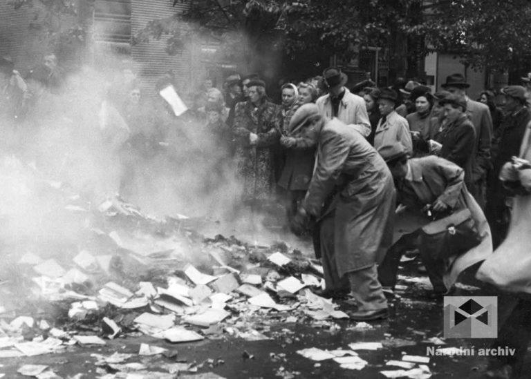 Na Václavském náměstí číslo 25, vyplenil dav Čechů německé vydavatelství Deutsche Arbeitsfront. Nacistické tiskoviny, plakáty a knihy létají z oken na mokrý chodník. Na hořící hranici končí i nacistické vlajky. Lidé mlčky přihlížejí, po šesti letech teroru a strachu je to osvobozující pocit.