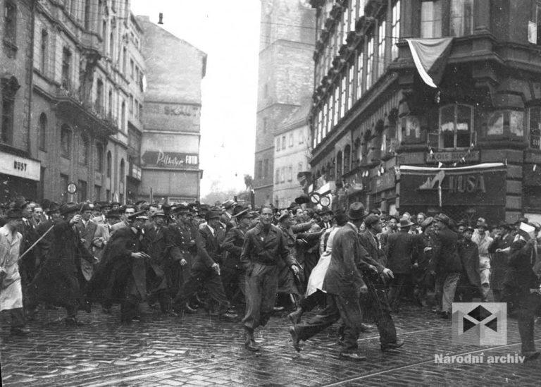 Na rohu Lazarské a Vodičkovy ulice se valí dav českých civilistů a mužů v různých uniformách směrem k budově soudu. Jsou vyzbrojeni noži, šavlemi, revolvery, puškami, dýkami. (Foto: Václav Chochola, archiv autora)