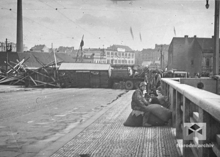 Čekání na nepřítele. Na Trojském mostě, důležitém přechodu přes Vltavu, byly brzy ráno postaveny celkem tři mohutné barikády. Hlavní se nacházela na holešovické straně, první od Kobylis měla zastavit pěchotu a odrazit nepřítele. Druhá barikáda měla krýt případný ústup obránců. Další barikády uzavřely nejbližší okolí mostu. Kolem sedmé hodiny ranní prováděly průzkum nad Holešovicemi německé stíhačky.