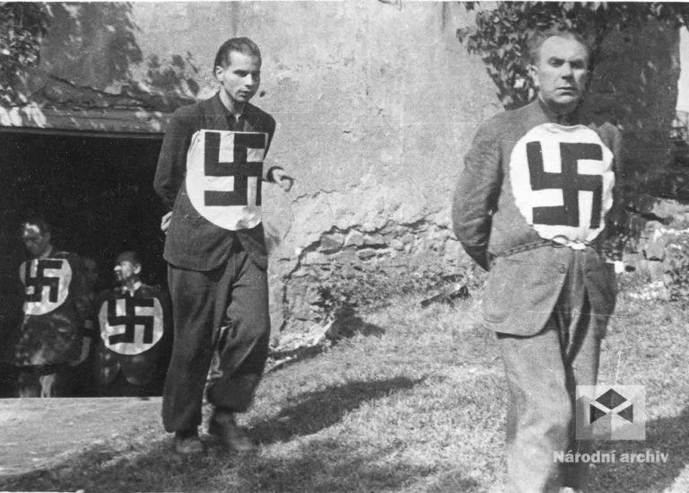 Němečtí civilní zajatci označení potupnými bílými kruhy s černými hákovými kříži, vystřiženými z velkých červených nacistických vlajek.