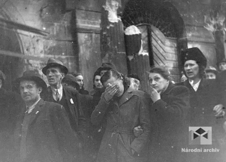 Šokovaní obyvatelé Prahy sledují se slzami v očích dílo zkázy. Proti nebi se rýsují ohořelé ruiny. Památný orloj je těžce poničen. Tam, kde byl hrob Neznámého vojína, leží ohořelé trámy, kusy plechů, zdiva, trosky rozbitých soch. Nacistům se podařilo po několikahodinovém ostřelování zasáhnout Staroměstskou radnici. Zničené hodiny se zastavily, vzápětí se zřítila střecha a radniční věž zcela vyhořela.